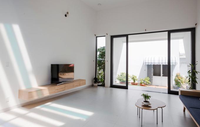 Công trình nằm trong khu của một đại gia đình nên chủ nhà có thể thoải mái mở cửa suốt ngày. Phần mái hiên rộng giúp che nắng nóng nhưng vẫn để ánh sáng, gió mát thổi vào nhà.